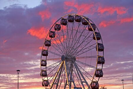 ferris wheel at amusement park against the red sky photo