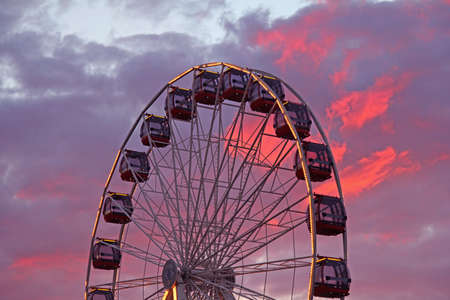 ferris wheel at amusement park and red clouds in the background photo