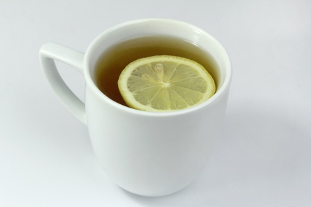 tea in white cup with lemon isolated on white photo