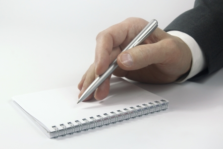 business hand with pen over notebook