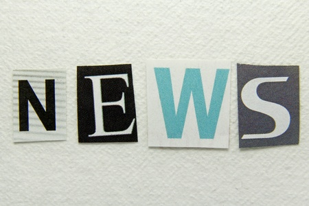 news word cut from newspaper on handmade paper background  photo