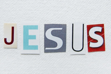 word jesus cut from newspaper on handmade paper texture  photo