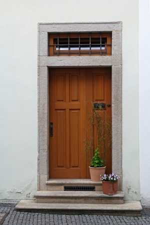 tenement: wooden door with stairs and flower in pots