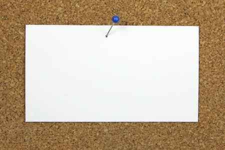 push pin holding a blank notecard on a cork board  photo