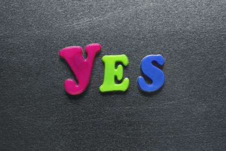 word yes spelled out using colored fridge magnets  Stock Photo