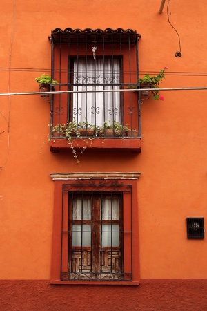 Intensive orange wall with two vintage windows photo