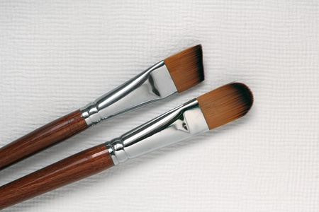 Two paint brushes on white paper photo