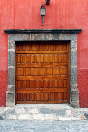 Wooden gate in red wall  typical mexican architecture Stock Photo - 21764366