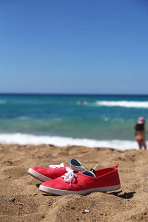swimming goggles: Swimming goggles and red sneakres on beautiful beach