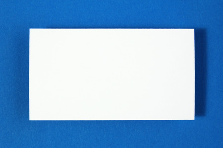 Blank business card on blue paper background photo