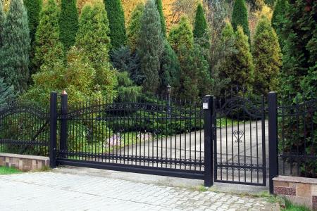 zwart smeedijzeren poort naar woning met tuin op de achtergrond