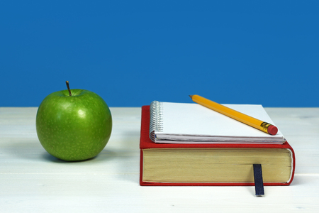green apple and book, with notebook and pencil on white wooden surface  photo