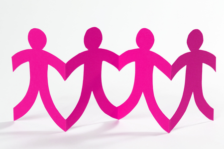 linked hands: Pink paper people in a row