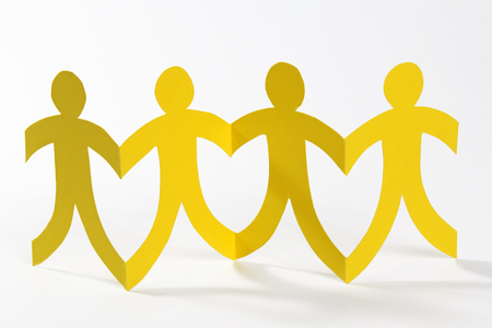 linked hands: Yellow paper people in a row