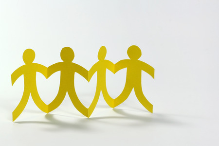 Teamwork, yellow paper people on white photo
