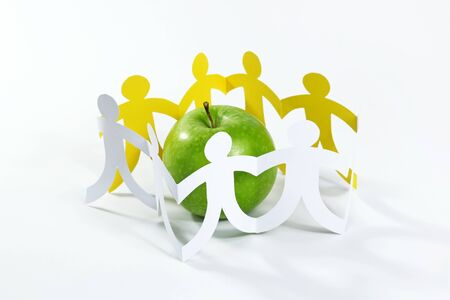 linked hands: Circle of paper people around the green apple