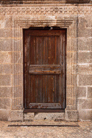ancient wooden door in stone wall  photo