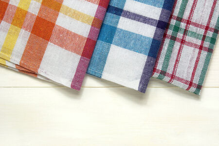 colorful dish towels on white wooden table  photo