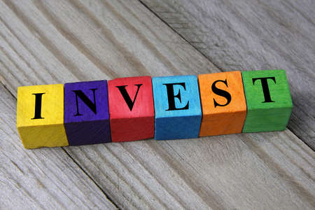 word invest on wooden colorful cubes photo