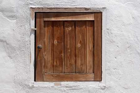 whitewashed: vintage wooden shutter in whitewashed wall Editorial
