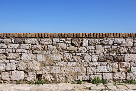 exterior wall: Stone old wall with sky in the background