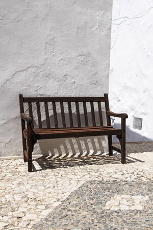 whitewashed: vintage wooden bench against whitewashed wall