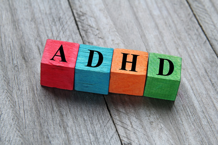 hyperactivity: concept of adhd word on wooden colorful cubes