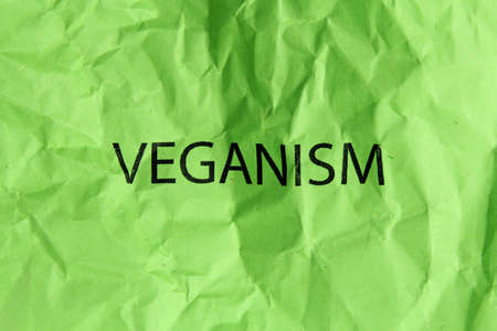 veganism: word veganism on green paper