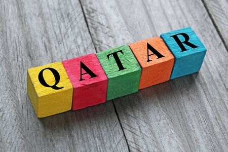 wor: word qatar on colorful wooden cubes