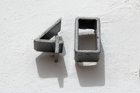 forty: Number forty on white wall Stock Photo