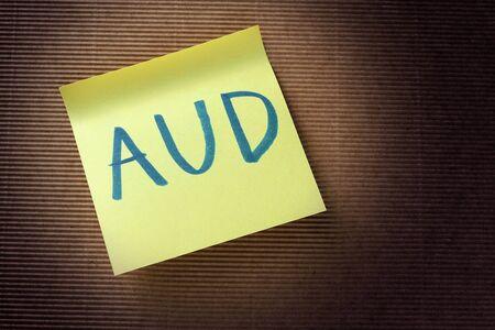 australian dollar notes: AUD Australian Dollar acronym on yellow sticky note