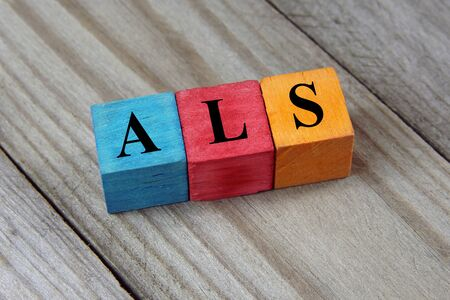 ALS Amyotrophic Lateral Sclerosis acronym on colorful wooden cubes