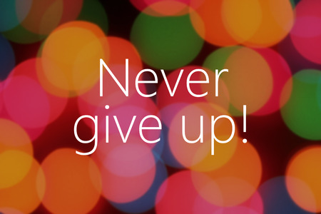 give: Never give up text on colorful background bokeh