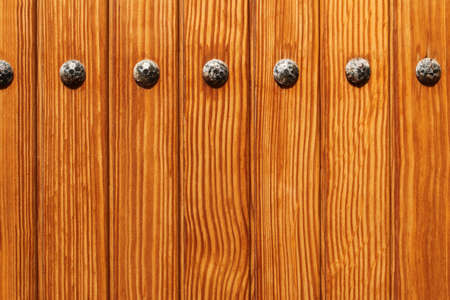 brown wooden boards with decorative rivets
