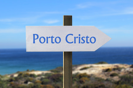 cristo: Porto Cristo road sign with seashore in the background