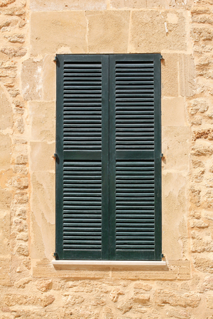 the shutter: window with green shutter in stone wall