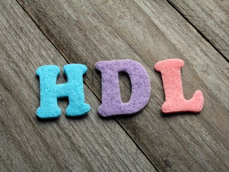 good cholesterol: HDL (high-density lipoprotein) acronym on wooden background