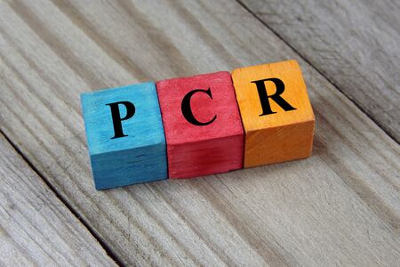 polymerase: PCR (Polymerase Chain Reaction) acronym on wooden background