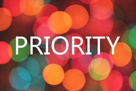 priority: priority word on colorful blurred bokeh background Stock Photo