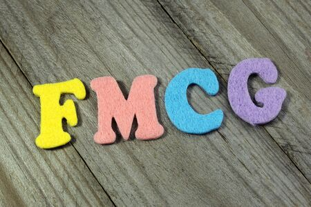 consumer goods: FMCG (Fast Moving Consumer Goods) business concept on wooden background