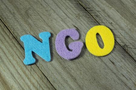 ngo: NGO (Non-Governmental Organization) acronym on wooden background