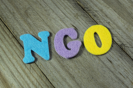 NGO (Non-Governmental Organization) acronym on wooden background
