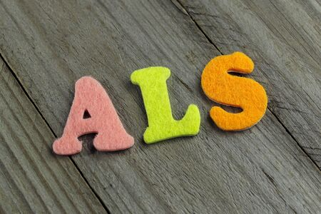 als: ALS (Amyotrophic Lateral Sclerosis) acronym on wooden background Stock Photo