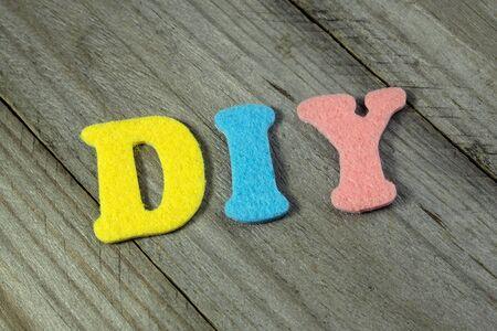 acronym: DIY (Do It Yourself) acronym on wooden background Stock Photo