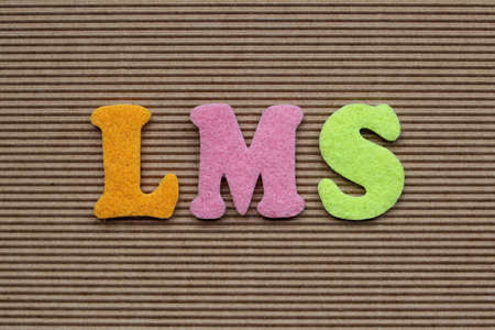 competences: LMS (Learning Management System) acronym on cardboard background Stock Photo
