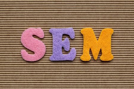 sem: SEM (Search Engine Marketing) acronym on cardboard background