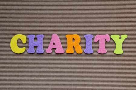 pay raise: charity word on cardboard background Stock Photo