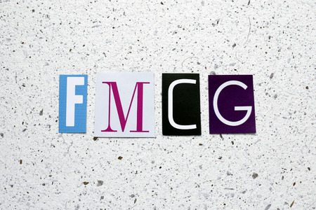 consumer goods: FMCG (Fast Moving Consumer Goods) acronym cut from newspaper on white handmade paper texture