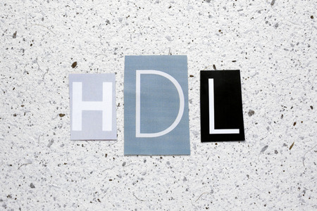 good cholesterol: HDL (high-density lipoprotein) acronym cut from newspaper on white handmade paper texture