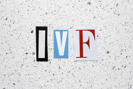 in vitro: IVF (In Vitro Fertilization) acronym cut from newspaper white handmade paper texture